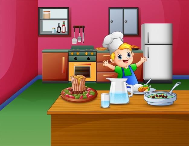 Il ragazzino sveglio in grembiule e cappello da cuoco sta preparando il cibo
