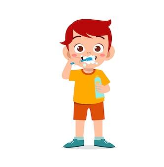 Ragazzino sveglio che si lava i denti e tiene il dentifricio