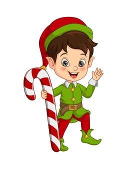 Ragazzino sveglio in costume da elfo di natale che tiene un bastoncino di zucchero