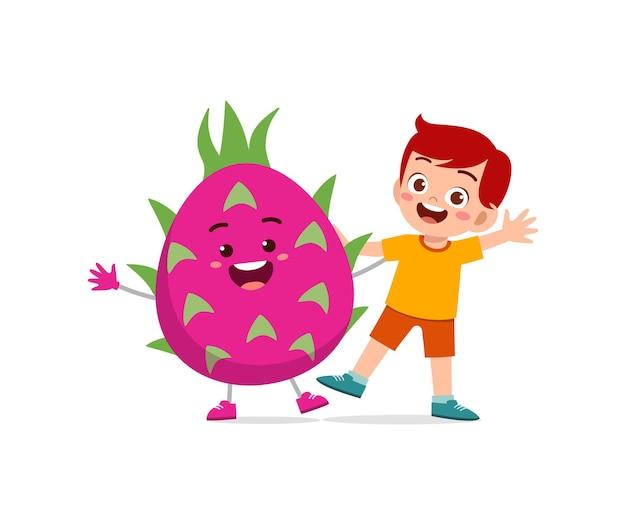 Il ragazzino carino sta con il personaggio del frutto del drago
