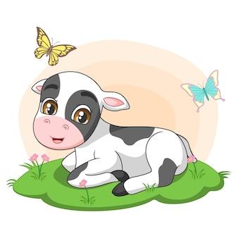 Piccola mucca sveglia che si siede nell'erba