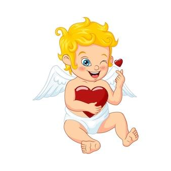 Piccolo cupido sveglio che abbraccia un cuore isolato su bianco