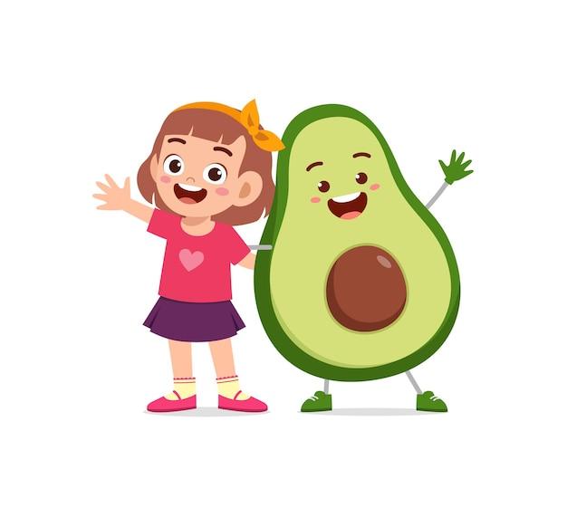 La bambina sveglia sta con il carattere dell'avocado