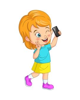 Bambina sveglia che prende selfie con uno smartphone