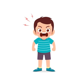 Il ragazzo sveglio del ragazzino sta e mostra l'espressione di posa arrabbiata
