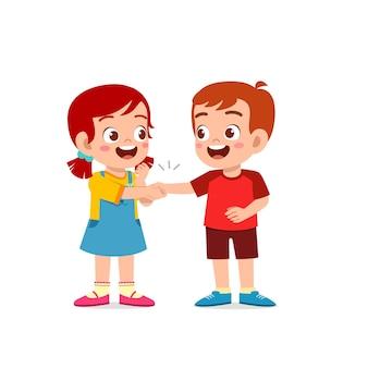 La bambina sveglia del bambino stringe la mano con la sua amica