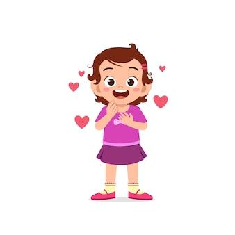 La ragazza sveglia del bambino mostra l'amore e l'espressione di posa felice