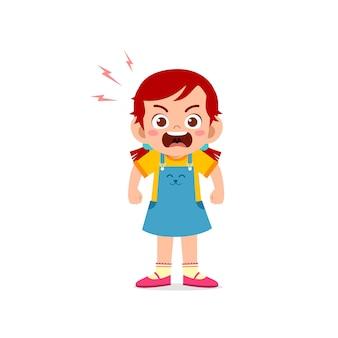 La ragazza sveglia del ragazzino sta e mostra l'espressione di posa arrabbiata