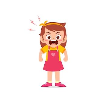 La ragazza sveglia del bambino sta e mostra l'espressione di posa arrabbiata