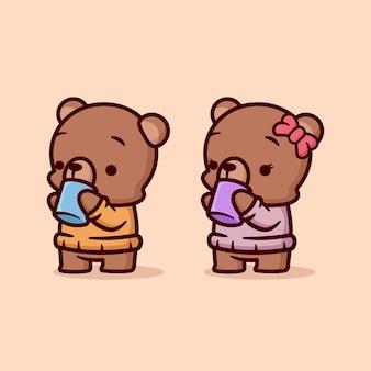 L'orso marrone sveglio maschio e femminile beve il cioccolato caldo