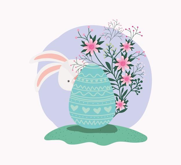 Simpatico coniglio con uova dipinte e fiori in giardino