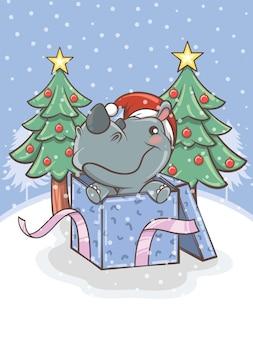 Rinoceronte carino con una confezione regalo e albero di natale - illustrazione del personaggio dei cartoni animati