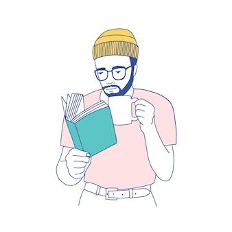 Ragazzo barbuto sveglio intelligente con gli occhiali che tiene tazza, bere caffè e leggere il libro