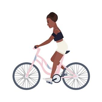 Adolescente sorridente sveglio vestito in pantaloncini e bicicletta di guida superiore. giovane donna o ciclista che pedala su una bici rosa