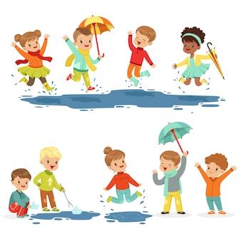 Piccoli bambini sorridenti svegli che giocano sulle pozzanghere