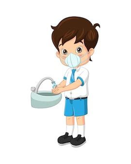 Ragazzo carino studente che indossa maschere per il viso lavarsi le mani