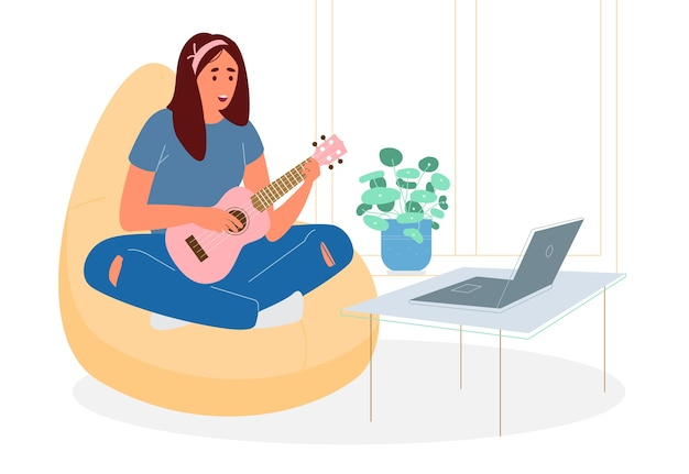 Ragazza adolescente carina seduta sulla sedia del sacchetto di fagioli con ritardi incrociati imparando a suonare l'ukulele online.