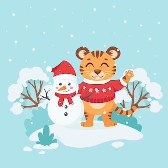 Cucciolo di tigre carino in un maglione e un pupazzo di neve su uno sfondo invernale