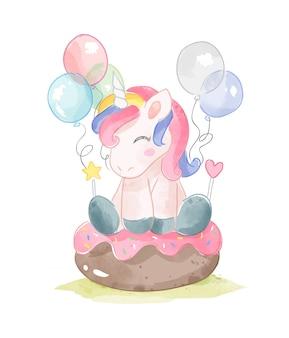 Unicorno sveglio che si siede sull'illustrazione della torta e dei palloni della ciambella