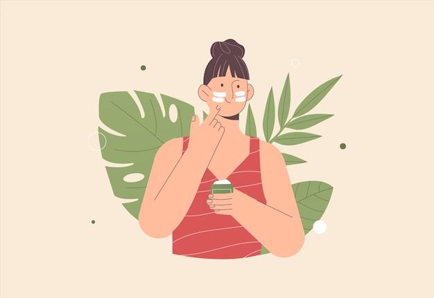 La giovane donna sveglia applica la crema e la pulizia o l'idratazione della sua pelle