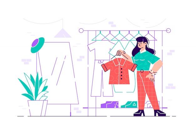 Giovane donna sveglia che sta davanti allo scaffale del gancio e che prova a scegliere attrezzatura. ragazza sorridente nello spogliatoio. personaggi femminili divertenti che tengono i vestiti. illustrazione moderna del fumetto in stile piano.