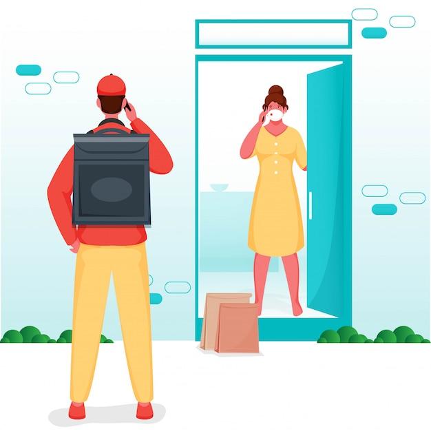 Fattorino che parla con donna del cliente dal telefono alla porta durante il pandemia di coronavirus (covid-19).