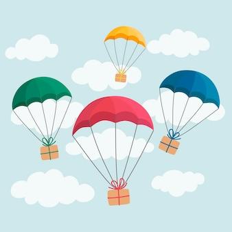 Concetto di consegna. paracadute colorati che trasportano scatole regalo su sfondo azzurro del cielo.