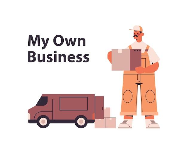 Fattorino in uniforme che tiene la scatola di cartone vicino alla logistica del carico di consegna espressa del furgone o al concetto di servizio postale