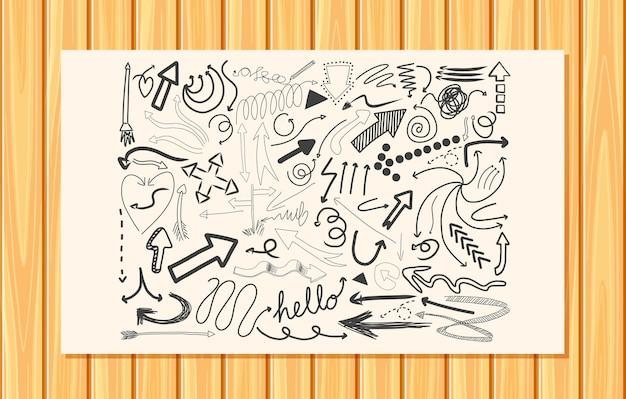Diversi tratti di doodle su una carta sul fondo della parete in legno
