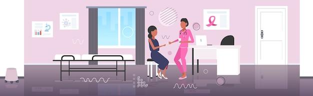 Medico che dà le pillole dei farmaci alla prevenzione della consapevolezza della malattia del giorno del cancro al seno del paziente della donna afroamericana