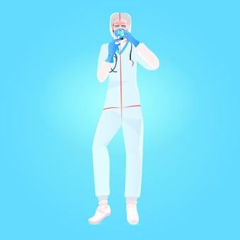 Medico in tuta protettiva e maschera che tiene la siringa con la fiala della bottiglia lotta allo sviluppo del vaccino