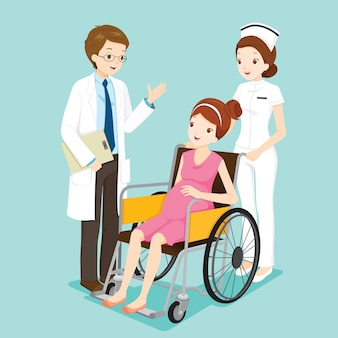 Medico che parla con incinta sulla sedia a rotelle e l'infermiera
