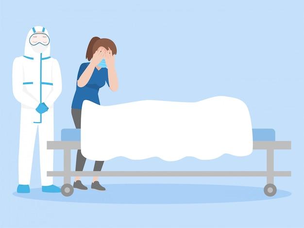 Medico con donna che piange su un cadavere coperto di lenzuolo bianco sul letto a ruote