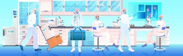 Team di medici in maschere e tute protettive che lavorano insieme nello sviluppo di vaccini di laboratorio medico