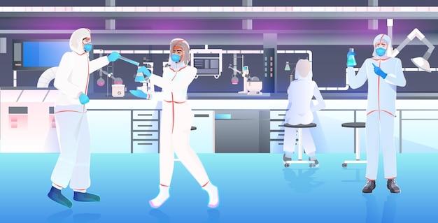 Team di medici in maschere e tute protettive che lavorano con provette per lo sviluppo di vaccini combattono contro covid-19