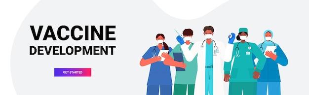 Squadra di medici in maschere mediche che tengono la siringa e la fiala della bottiglia coronavirus sviluppo del vaccino concetto di campagna di immunizzazione medica banner orizzontale