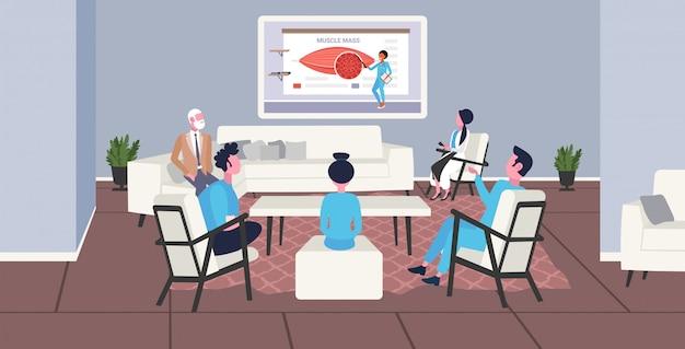 Team di medici che guardano la presentazione televisiva online sull'assistenza sanitaria di massa muscolare di anatomia dei muscoli umani