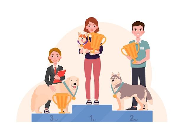 I cani con medaglie vincenti stanno sul piedistallo del vincitore con i loro proprietari in possesso di coppe d'oro