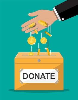 Scatola per donazioni con monete d'oro. beneficenza, donazione, aiuto e concetto di aiuto