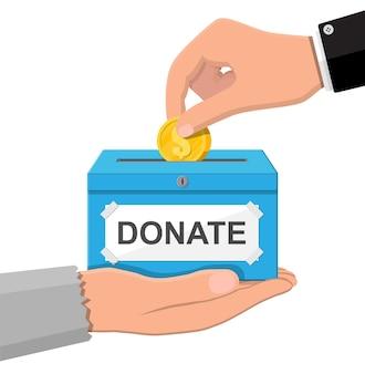 Scatola per donazioni con monete d'oro. beneficenza, donazione, aiuto e concetto di aiuto.