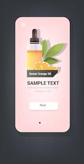 Lasciando cadere la bottiglia di vetro essenziale di olio di arancia dolce con frutta e foglie di arancia viso naturale corpo rimedi bellezza concetto smartphone schermo mobile app verticale