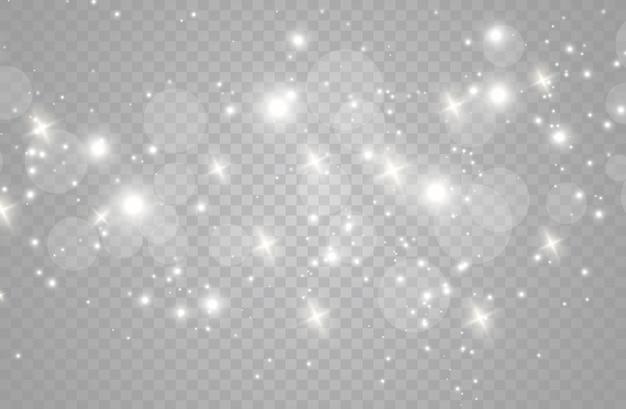 Le scintille di polvere e le stelle dorate brillano di una luce speciale. brilla su uno sfondo trasparente. effetto luce natalizia. scintillanti particelle di polvere magica.