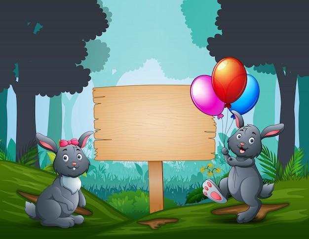 I coniglietti pasquali con un cartello in legno sulla natura