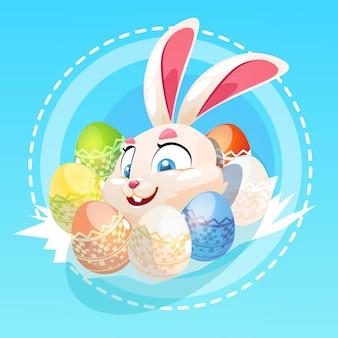 La tenuta del coniglio di pasqua ha decorato la cartolina d'auguri variopinta di simboli di festa dell'uovo