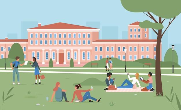 Studenti felici di scena di istruzione che si siedono sull'erba verde del parco di estate che studiano insieme