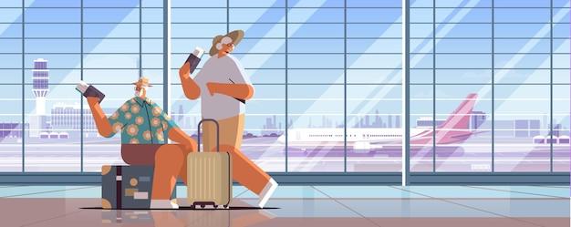 Coppia anziana di turisti nonni con bagagli in possesso di passaporti e biglietti pronti per l'imbarco all'aeroporto