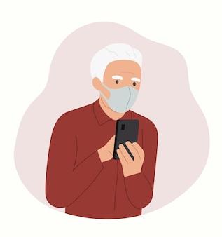 L'uomo anziano in maschera esamina lo smartphone.