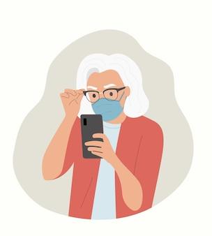 La donna anziana in maschera esamina lo smartphone.