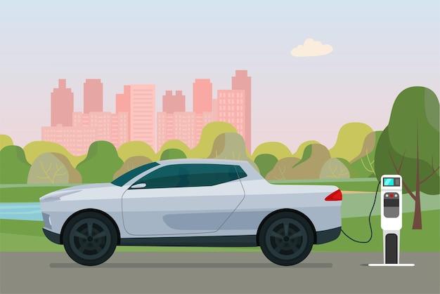 Pick-up elettrico in una città. l'auto elettrica è in carica, vista laterale.