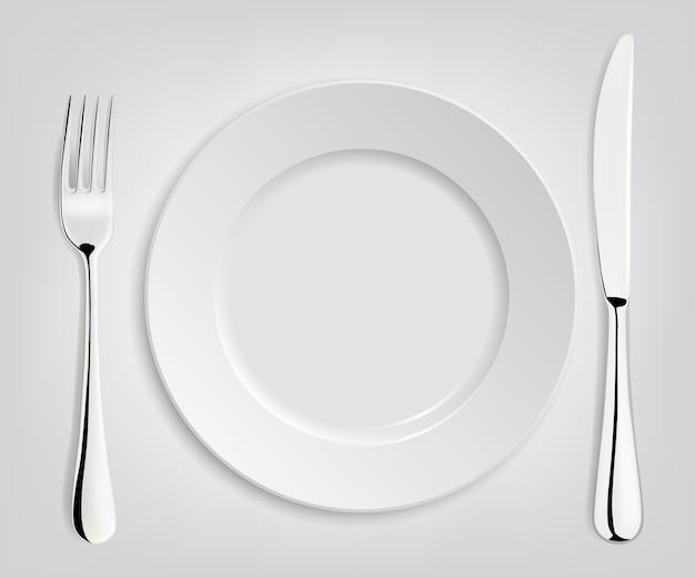 Piatto vuoto con coltello e forchetta isolato su bianco.